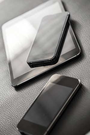 Technology, electronics  Mobile phone and tablet on the leather sofa photo