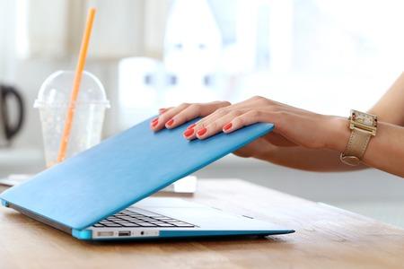 tabla de surf: Chica con un ordenador port�til en la mesa Foto de archivo