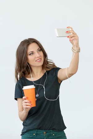 Cute, attractive girl with mobile phone and headphones photo