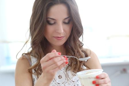 Cute, attractive woman eating yoghurt photo