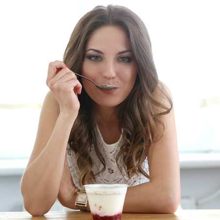 woman with ice cream: Cute, attractive woman eating yoghurt Stock Photo
