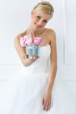 Wedding  Attractive bride holding pot with beautiful roses photo