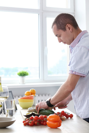 Food  Happy, attractive man at kitchen photo