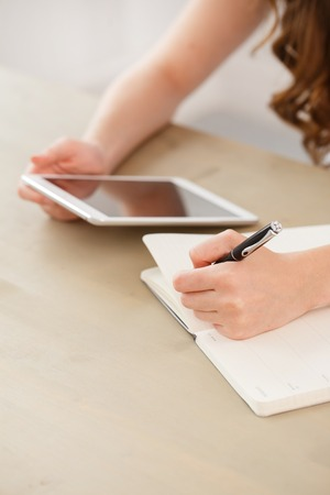 Home, study  Woman by the table with tablet photo