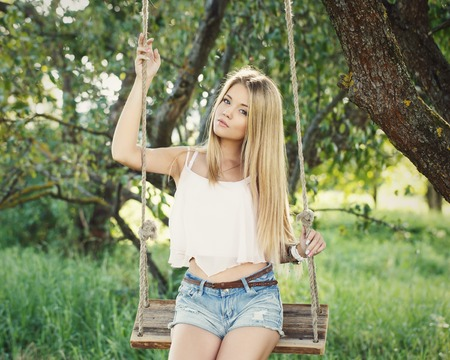 Summer, warm. Cute, young girl on a swing photo