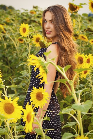 Cute girl in the field full of sunflowers photo