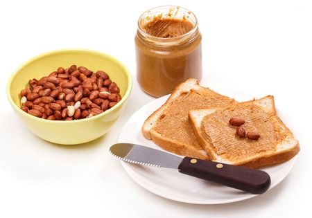 Peanut butter with heap of peanuts on the table photo