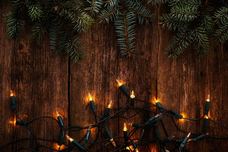 light green: Christmas, New Year. Fir with garland on a wooden table