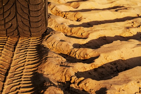 Deep trace of wheels on a sandy road photo