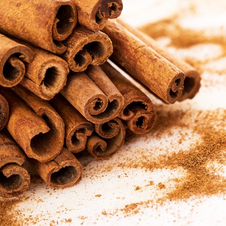 cinnamon bark: Stack of cinnamon with its dust around it over a white background