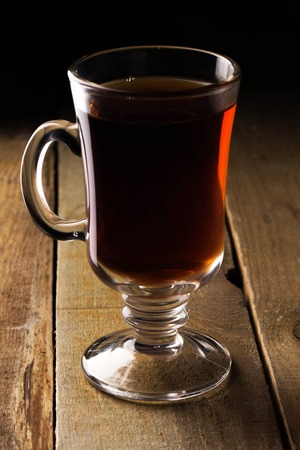 Glass of tea on a wooden sorface over a dark background photo