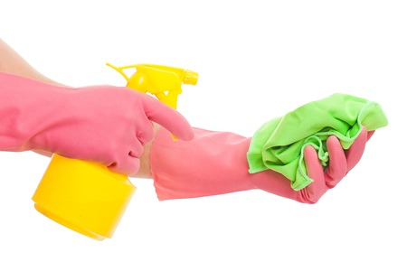 gloving up: Hand in a pink glove holding spray bottle and sponge isolated over white background Stock Photo