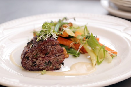 Dish with delicious meat cutlet and garnish that consists of vegetables, sauce and some vermicelli photo