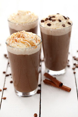 Eiskaffee mit Sahne und Kaffeebohnen auf einem weißen Tisch Standard-Bild