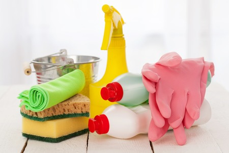 Bright colorful cleaning set on a white wooden table Standard-Bild