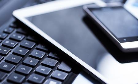 Closeup Bild von einer Tastatur mit einem Telefon und Tablet darüber liegenden Standard-Bild