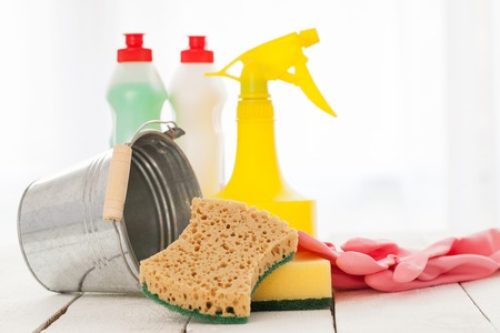 bright housekeeping: Bright colorful cleaning set on a white wooden table Stock Photo