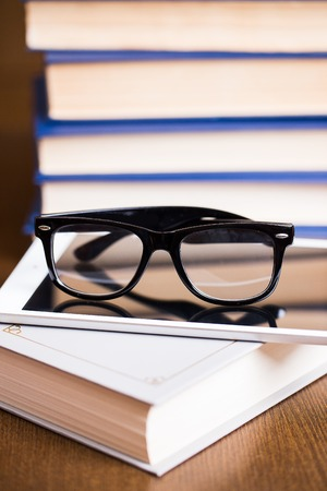 cramming: Picture of black glasses on a white book and a tablete