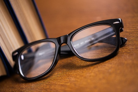 cramming: Picture of black glasses on a blue book on a wooden table