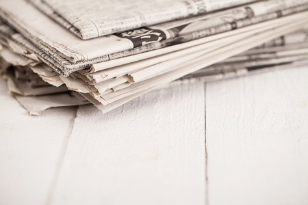 newspaper stack: Pile of black and white newspapers on a wooden table