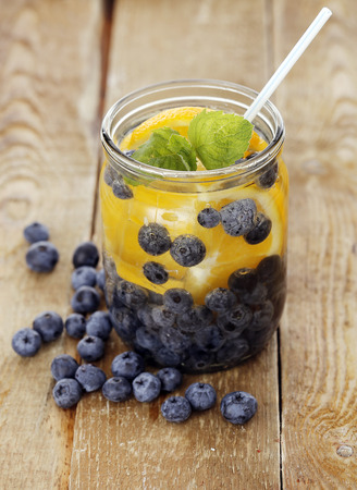 A jar full of cold drink with bilberry and lemon with a straw over a wooden surface photo