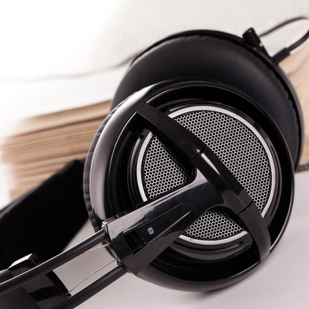 Big headphones and book on a white background photo