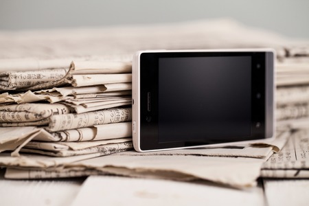 Pile of black and white newspapers with a black smartphone on a wooden table photo