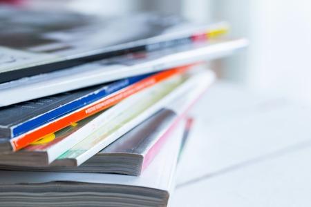 Haufen von bunten Zeitschriften auf einem weißen Tisch Standard-Bild