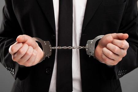 manacles: Hombre de negocios en traje con esposas cerradas en sus manos