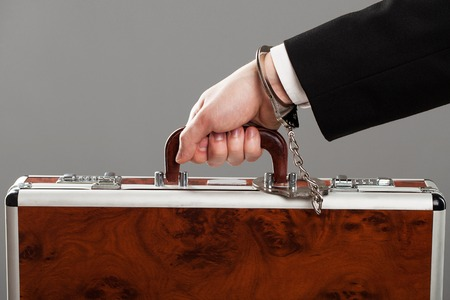 Case attached to businessmans hand with metal handcuffs photo