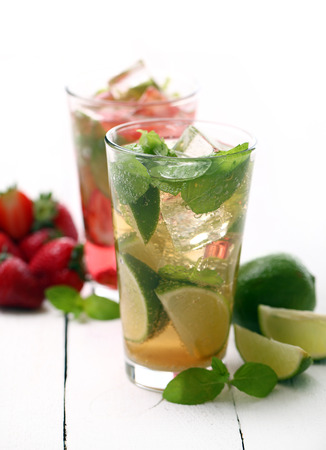 Fresh tasty strawberry and mint mojito on a white wooden table photo