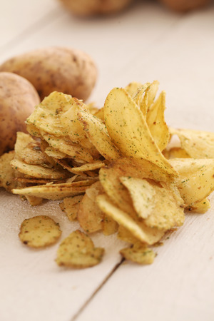 Rustic fresh unpeeled potatoes and chips on a white wooden table photo