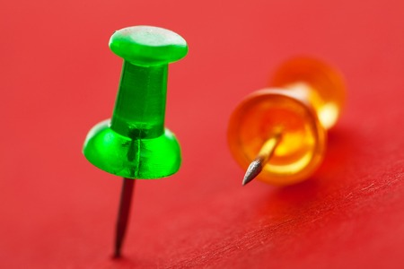 Green and orange pushpins on a red surface photo
