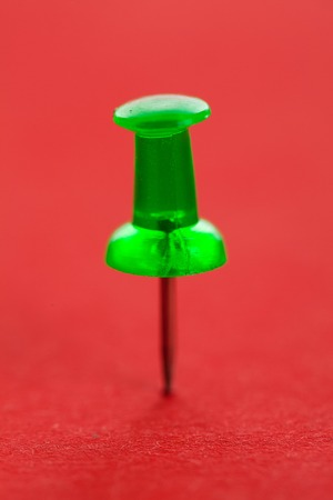 Green pushpin on a red surface photo