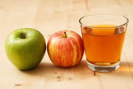 Glass of apple juice with apples on the table photo