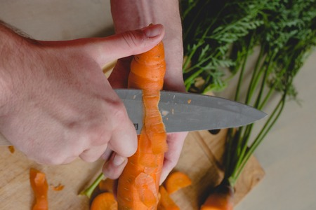 Food, natural. Guy cuts carrot photo