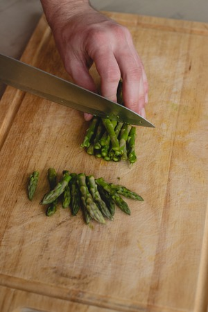 Food, natural. Guy cuts asparagus photo