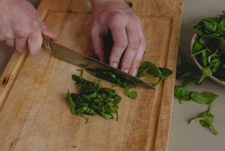 Food, natural. Guy cuts spinach photo
