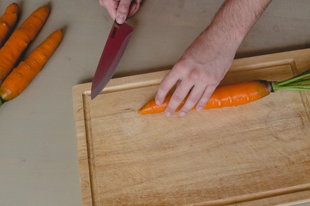 Guy cuts carrot photo