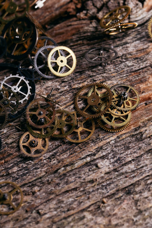 Details, technology. Heap of small gears on a wooden table photo
