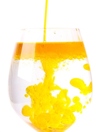Olive oil in a glass of water Imagens