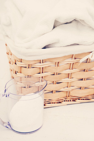 Laundry. Wicker basket with dirty towels and powder photo