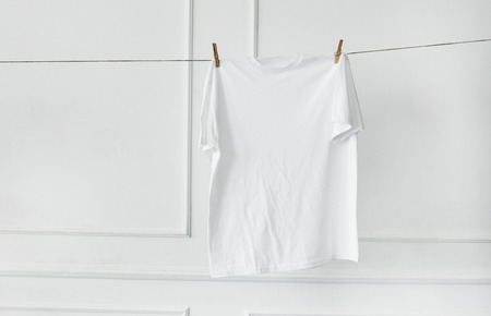 dry clean: Dry, clean. White t-shirt hanging by the wall