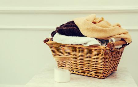 lavadora con ropa: Servicio de lavander�a. Cesta de mimbre con toallas sucias