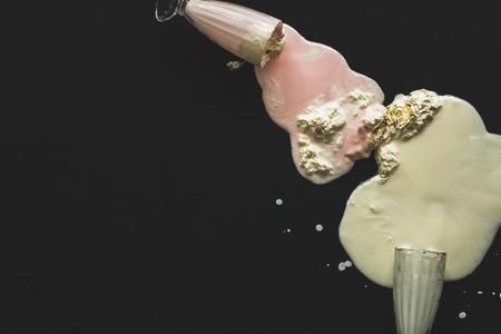 poured: Poured milkshakes on a black background Stock Photo