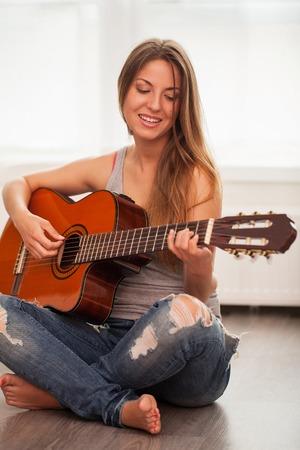 niñas jugando: Hermosa mujer caucásica joven en la guitarra ocasional de juego Foto de archivo