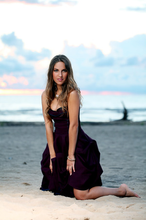 20 24 years: Beautiful girl with brown hair who is wearing a dark purple dress is posing at a beach