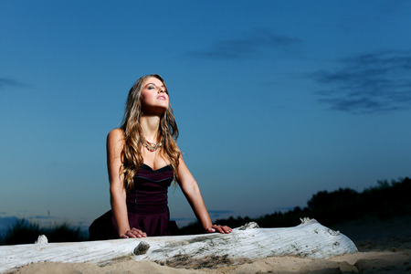 20 24: Beautiful girl with brown hair who is wearing a dark purple dress is posing at a beach over a dark sky background