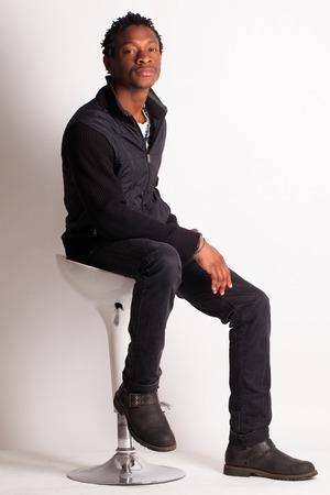 black guy: Chico negro hermoso que se sienta en una silla sobre fondo blanco