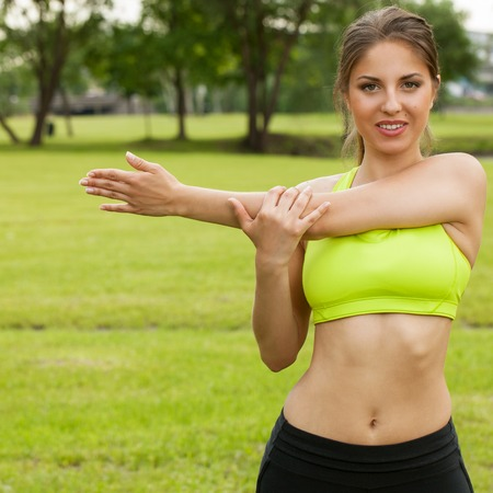 Beautiful young caucasian woman in fitness wear working out in a park photo